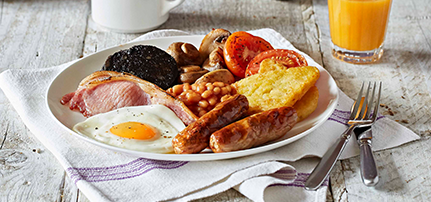 Full Premier Inn breakfast on a plate - showing sausages, bacon, fried egg, baked beans, hash brown, mushrooms and tomato.